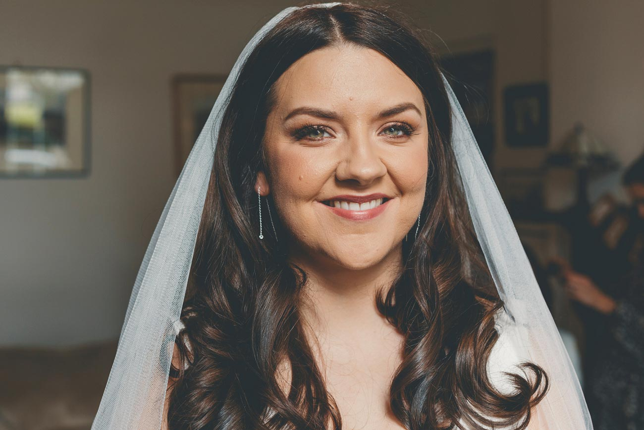 smiling bride with long wavy hair and veil