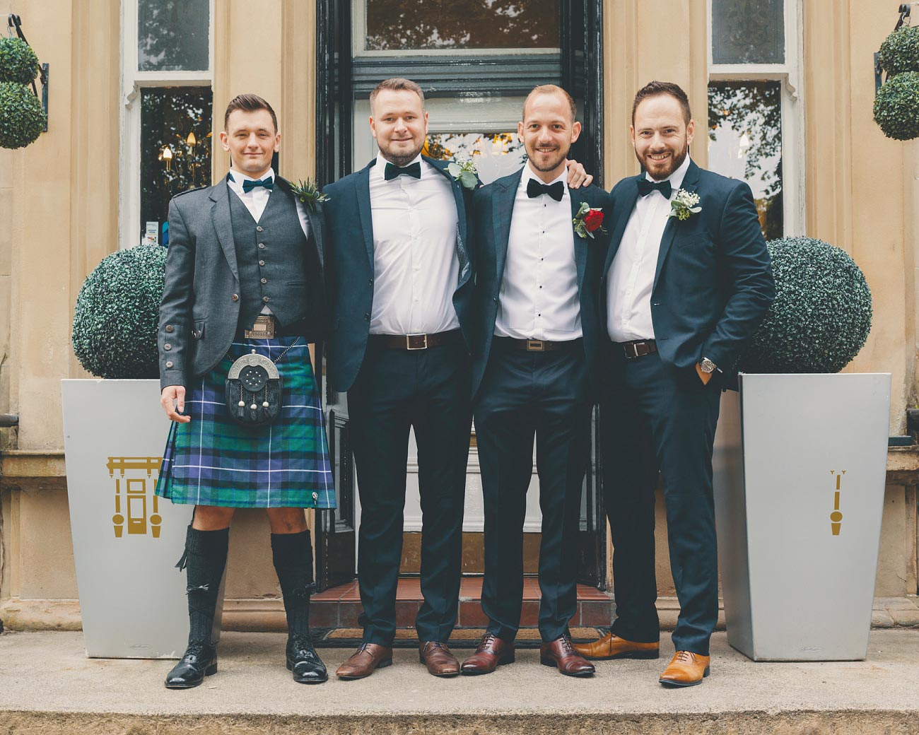groom with groomsmes in suits and kilt, brown leather shoes